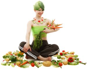The picture of a happy woman, holding and surrounded by her vegetables.