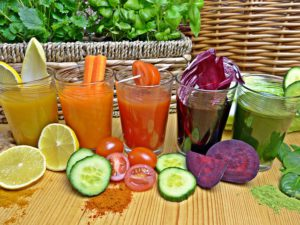 The images of glasses filed with fruit and veggie smoothies, with more fruits and veggies before them.