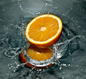 The wonderful picture of an orange nestling in a foundatin of fresh water.