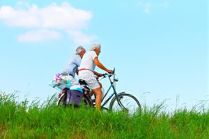 The colorful picture of two seniors happily riding their bikes in the country side.