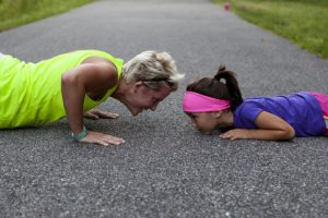 The picture of an older woman and little girl doing pushups in the park.