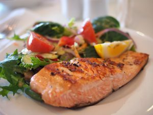 Picture of a well balanced meal, illustrating salmon, and healthy sides.