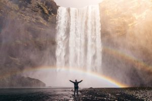The wonerful picture of a man expreeing his stress free life near a waterfall, at the end of a rainbow.