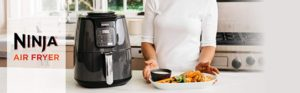 The Picture of a Ninja air fryer sitting on a kitchen counter in front of some amazing dish's of food.
