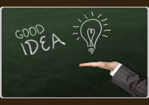 The chalkboard image of a light bulb over a hand, illustrating good idea.