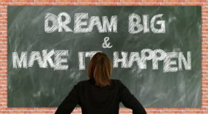 The picture of the chalkboard with a person in front of it, stating dream big and make it happen.