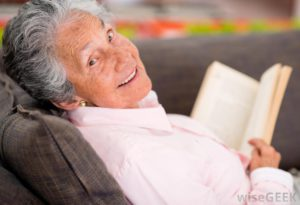 The amazing picture of an eldery woman reading and smiling.