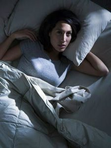 The picture of a woman laying in bed experiencing a sleepness night.
