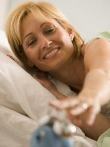 The picture of a woman awakening with a vibrant smile, from a good nights sleep.