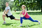 The picture of two people doing stretch exercise, is a park.