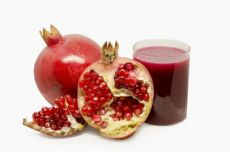 The amazing picture of a pomegranite portrayed in a half and in a juice.