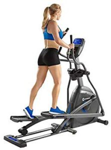 The picture of a very well toned woman on her Elliptical trainer.