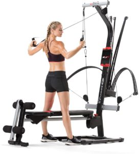 The picture of a woman engaging her Bowflex, PR 100, home gym.