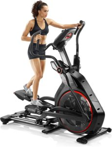 The amazing picture of a bowflex elliptical machine, with a woman engaging it.